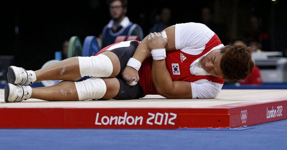 01.ago.2012 - Sul-coreano Sa Jae-Hyouk fica caído no chão depois de quebrar o braço em prova de levantamento de peso