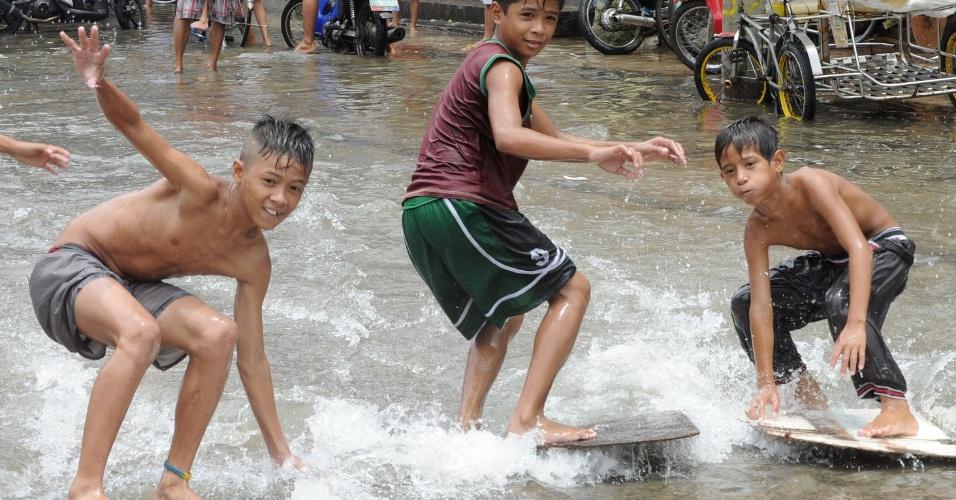 2.ago.2012 - Crianças 'surfam' em rua alagada de Navotas, região do subúrbio de Manila, capital das Filipinas