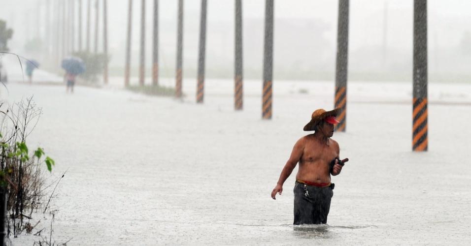 2.ago.2012 - Morador de Wuche, em Taiwan, caminha em rua alagada após a passagem do tufão Saola. Uma mulher morreu e voos foram cancelados no país por conta das tempestades