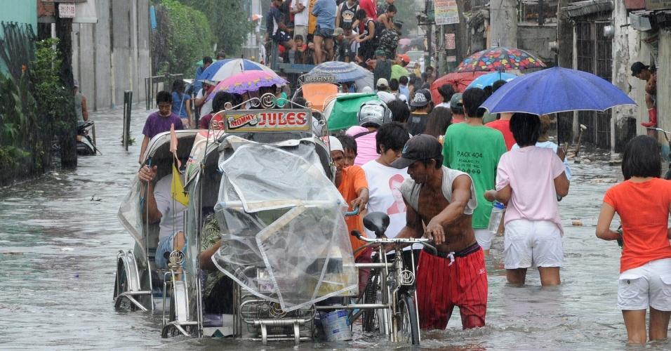 2.ago.2012 - Moradores caminham em área alagada de Navotas, região do norte de Manila, capital das Filipinas