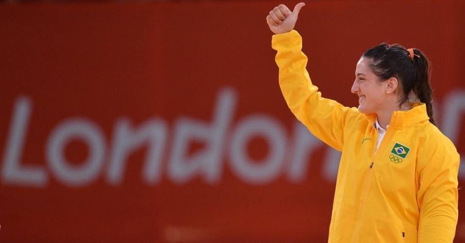 Mayra Aguiar sorri e acena positivamente enquanto caminha para receber a medalha de bronze