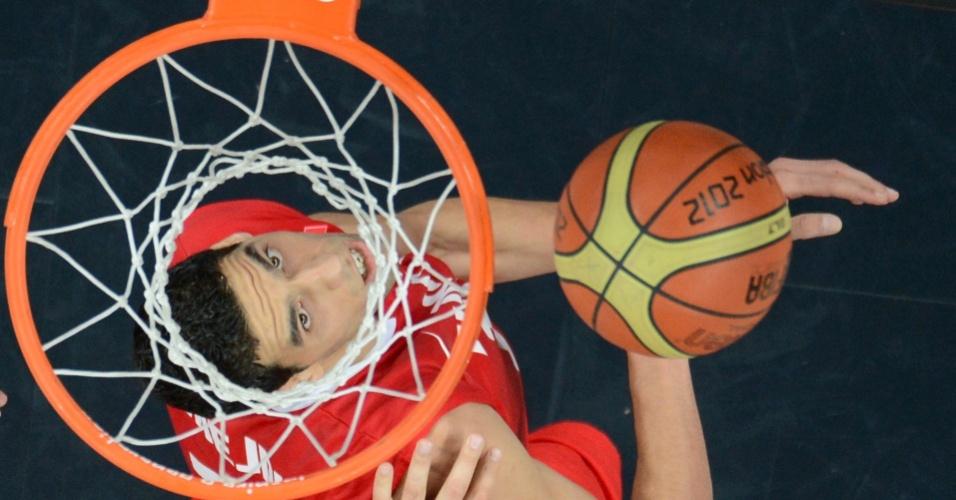 Pivô da seleção de basquete da Tunísia, Salah Mejri, observa bola chegar na cesta durante jogo contra a Argentina