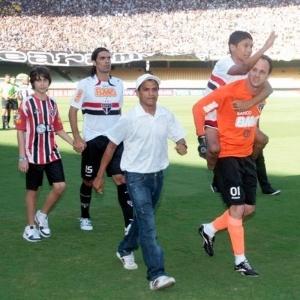 Rogério carrega menino Carlos Roney antes da partida entre Ceará x São Paulo, no Castelão