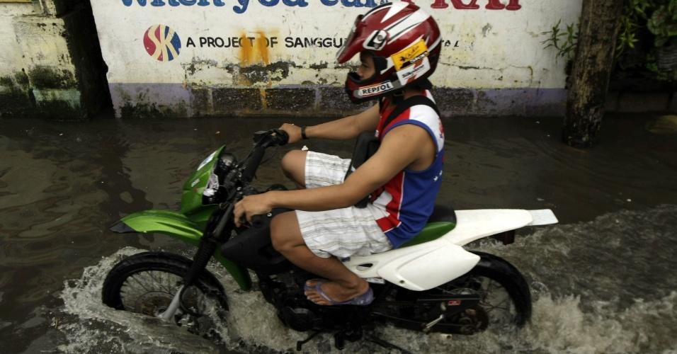 3.ago.2012 - Motorista passa por rua alagada de Navotas, ao norte de Manila (Filipinas), nesta sexta-feira (3). As autoridades locais anunciaram que o número de mortes causadas pelo tufão Saola subiu para 37