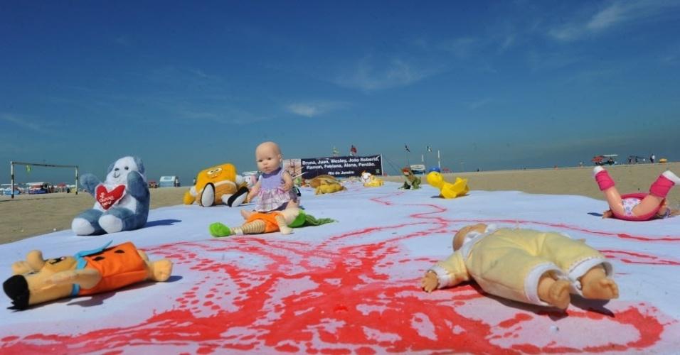 3.ago.2012 - ONG Rio de paz leva para a praia de Cobacabana, no Rio de Janeiro, um lençol branco de 30 metros de comprimento manchado de tinta vermelha e repleto de brinquedos, nesta sexta-feira . O ato defende a redução de homicídios no Rio, especialmente de crianças durante operações policiais