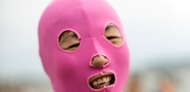 Chinesas usam máscaras para proteger rostos do sol enquanto curtem praia em Qingdao, na China
