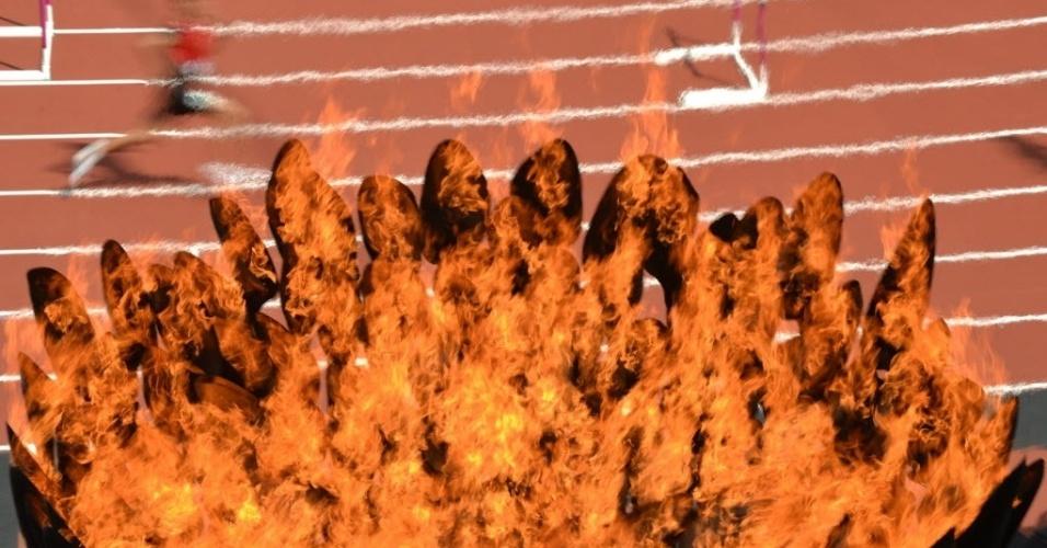 Imagem mostra em detalhes a chama olímpica durante competição de atletismo na pista