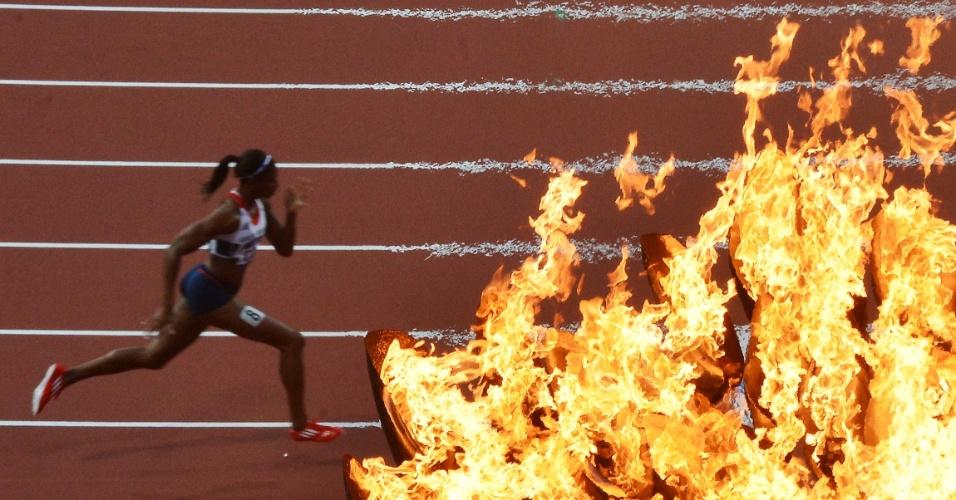 Atleta britânica Shana Cox durante prova semifinal dos 400 m feminino; no detalhe, a pira olímpica