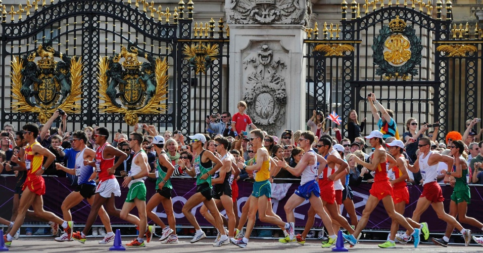 Atletas da marcha atlética passam pelos portões do Palácio de Buckingham em Londres