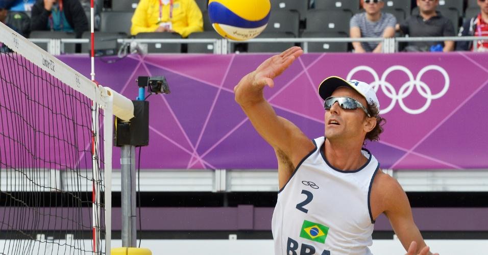Emanuel sobe para cortar a bola em partida contra dupla da Alemanha nas oitavas de final do vôlei de praia