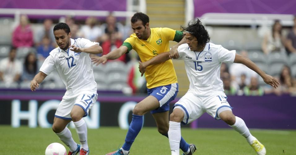 Sandro tenta escapar da marcação de Peralta (esq.) e Roger Espinoza  durante partida entre Brasil e Honduras pelas quartas de final dos Jogos