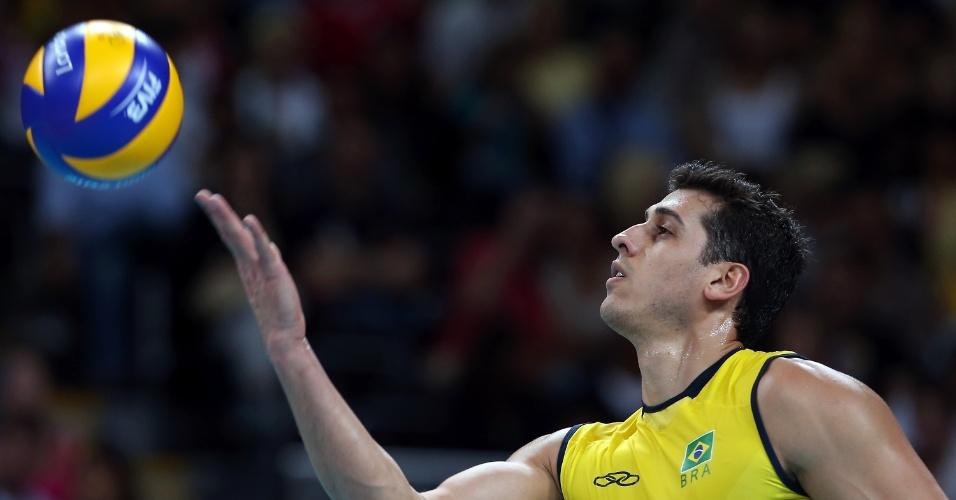Sidão, meio de rede do Brasil, joga a bola para cima para sacar, durante a partida contra a Sérvia