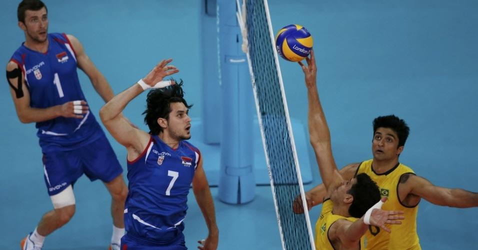 Sidão, meio de rede do Brasil, tenta, com uma mão, bloquear o ataque de Nikola Kovacevic, da Sérvia