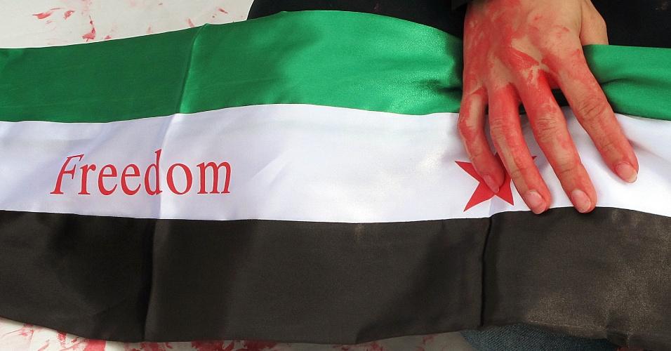 Vestidos com roupas com as cores da bandeira síria, imigrantes sírios que vivem na Inglaterra pediam que torcedores entrassem na arena do hipismo com selo grudado que pedia liberdade para o país