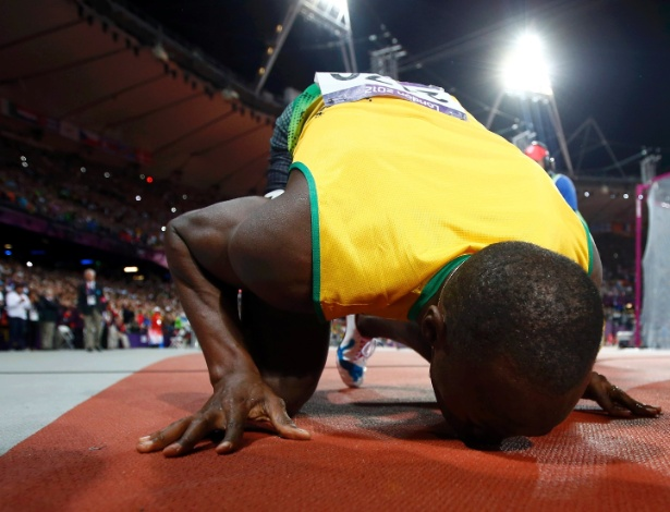 Bolt beija pista do Estádio Olímpico de Londres, após conquistar a medalha de ouro
