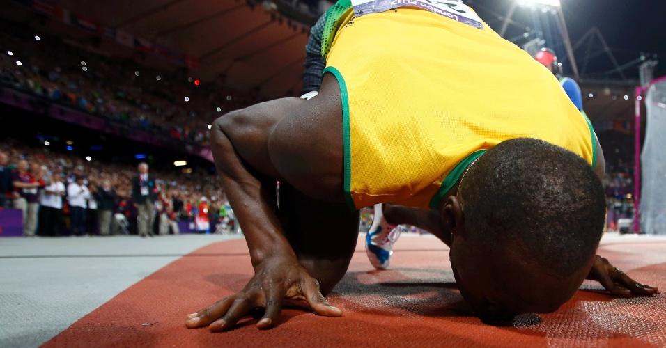 Jamaicano Usain Bolt beija pista do Estádio Olímpico de Londres, após conquistar a medalha de ouro na prova dos 100 m rasos