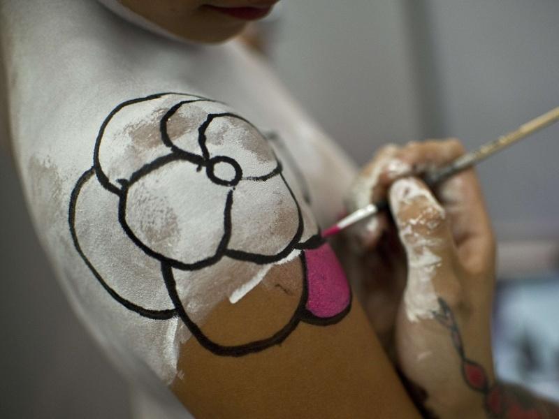 3.ago.2012 - Artista tatua flor em mulher durante a Expo Tatoo Art Mex, convenção de tatuagens realizada na Cidade do México, no México