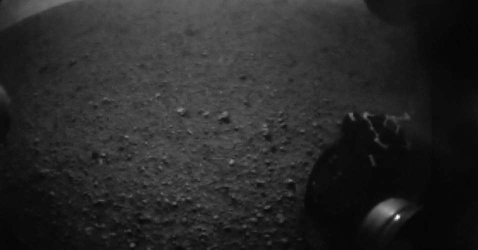 6.ago.2012 - A imagem, capturada da Nasa TV, mostra a roda do robô Curiosity em uma cratera de Marte. A missão não tripulada estudará a possibilidade de ter havido vida no planeta vermelho