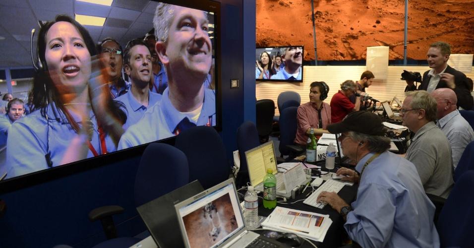 """6.ago.2012 - Trabalhadores do laboratório da Nasa (agência espacial americana) comemoram o pouso do robô Curiosity em uma cratera de Marte. A descida pela atmosfera do planeta foi chamada de """"sete minutos de terror"""" por conta das manobras de alto risco que reduziram a velocidade da nave de 20 mil km/h para apenas 1m/s, o que permitiu que as rodas do jipe-robô tocassem a superfície da cratera suavemente"""