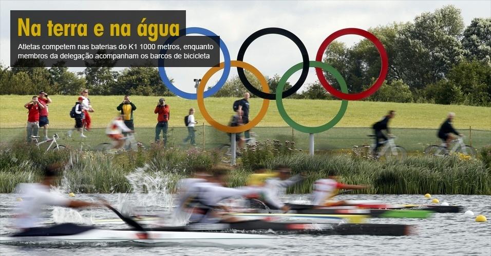 Atletas competem nas baterias do K1 1000 metros, enquanto membros da delegação acompanham os barcos de bicicleta