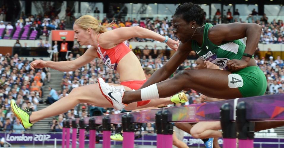 Austríaca Beate Schrott e nigeriana Seun Adigun competem em bateria dos 100 m com barreira