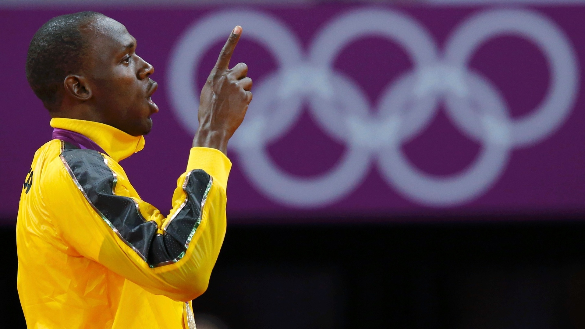 Bicampeão olímpico dos 100 m rasos, jamaicano Usain Bolt faz sinal de número 1