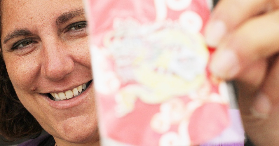 Colecionadora exibe broche que conseguiu em troca nas proximidades das instalações dos Jogos de Londres