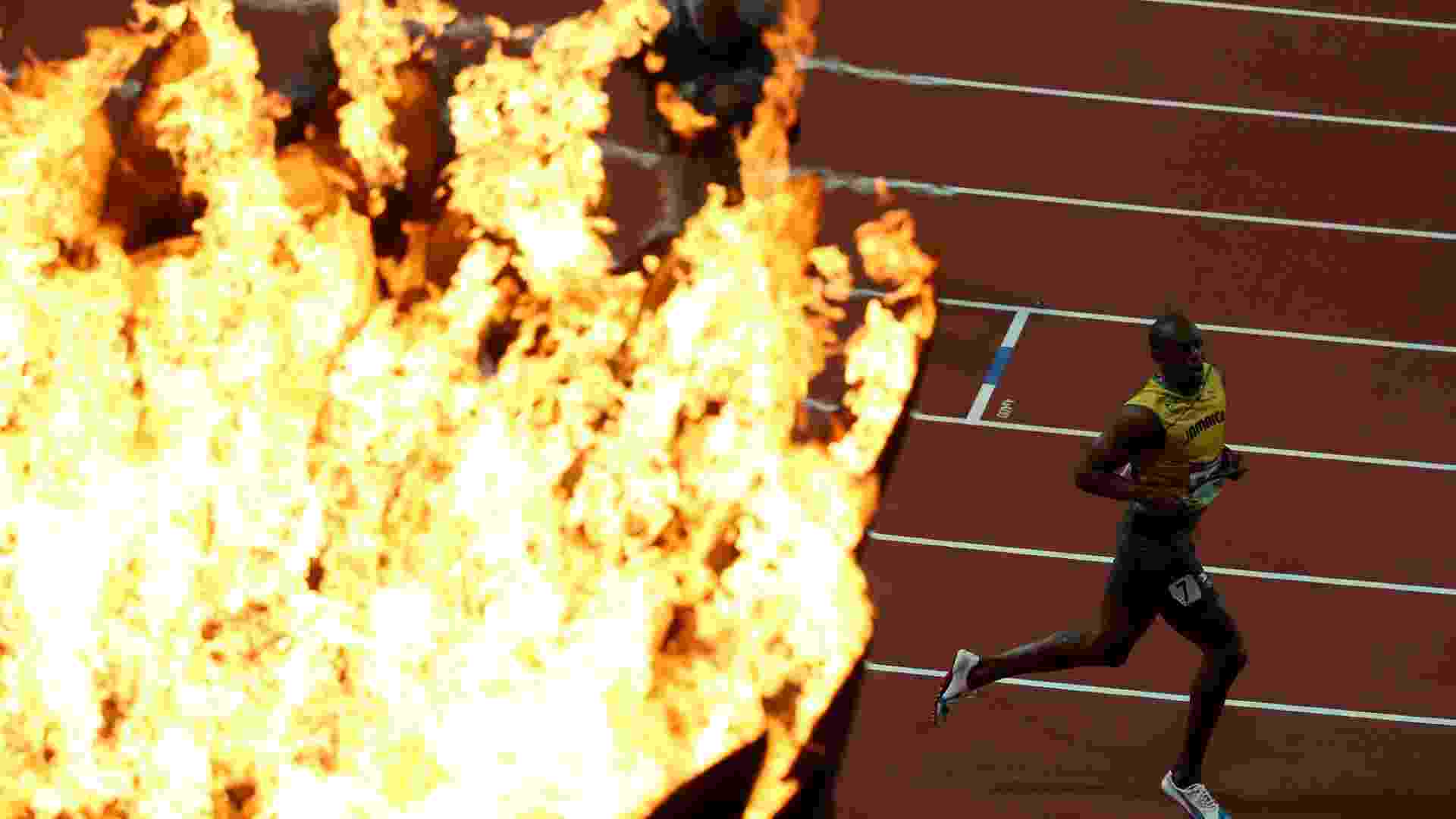 Com a pira olímpica em primeiro plano, Usain Bolt comemora o bicampeonato olímpico nos 100 m rasos em Londres - Jeff J Mitchell/Getty Images
