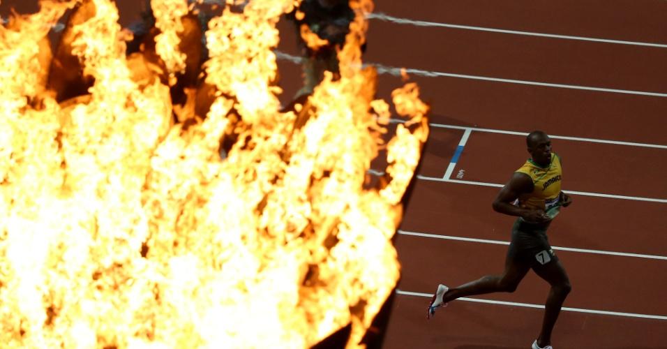 Com a pira olímpica em primeiro plano, Usain Bolt comemora o bicampeonato olímpico nos 100 m rasos em Londres