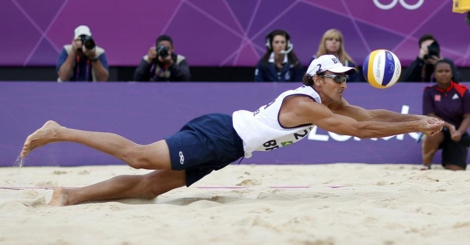 Emanuel se joga na areia para fazer defesa durante a vitória de dupla brasileira sobre poloneses