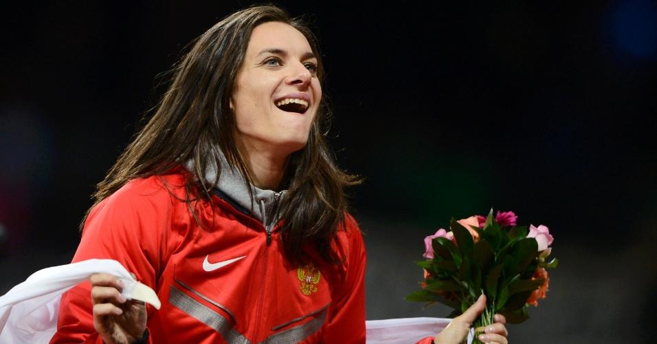 Musa Yelena Isinbayeva sorri após receber um buquê de flores, em cerimônia de premiação do salto com vara em Londres