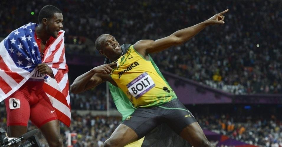 Terceiro colocado, Justin Gatlin, com a bandeira dos EUA, acompanha de perto a gesto característico de Usain Bolt, bicampeão olímpico dos 100 m rasos