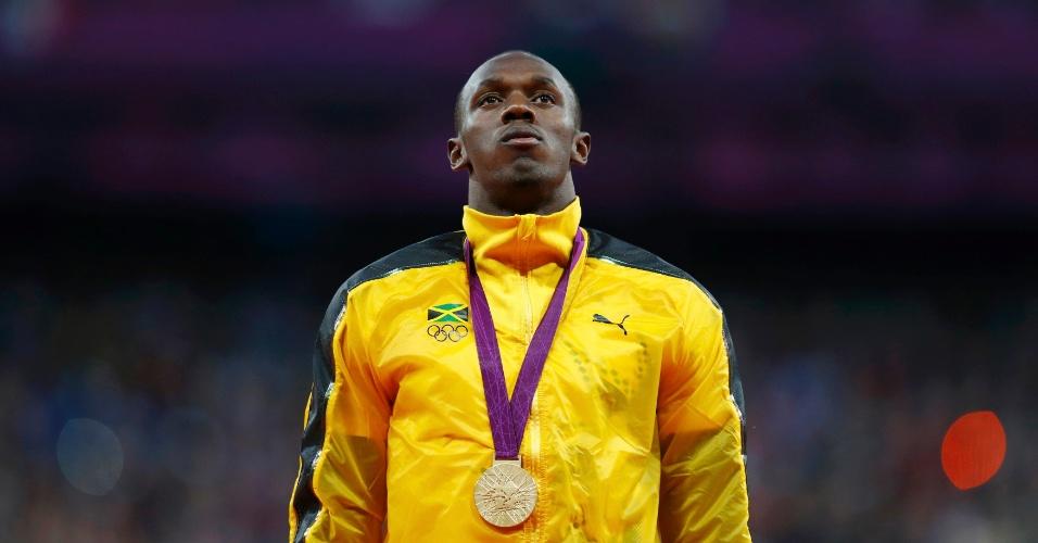 Usain Bolt acompanha execução do hino nacional jamaicano, em cerimônia de premiação dos 100 m rasos nos Jogos de Londres