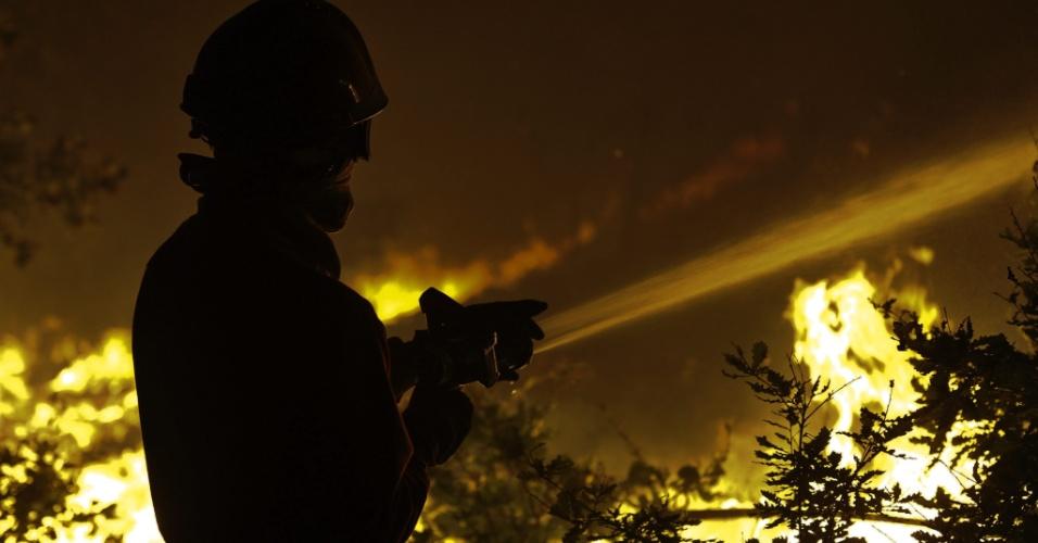 7.ago.2012 - Bombeiro tenta controlar chamas de incêndio florestal em Oliveira do Hospital, em Portugal