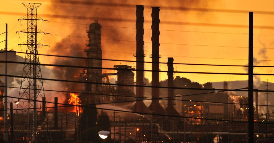 7.ago.2012 - Bombeiros combatem chamas em refinaria de óleo da Chevron em Richmond, na Califórnia (EUA), nesta segunda-feira (6). A coluna de fumaça obrigou as autoridades locais a pedirem para os moradores ficarem dentro de casa na noite desta segunda. A refinaria que pegou fogo tem 110 anos e uma pessoa ficou ferida por conta do incêndio