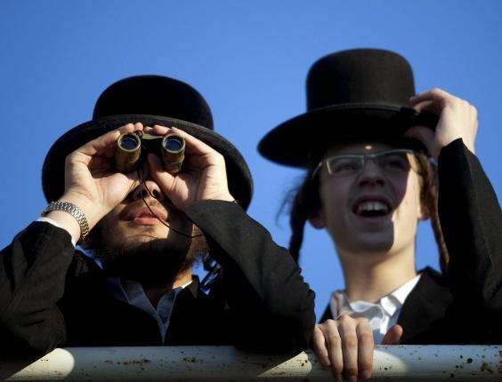 7.ago.2012 - Dois judeus ultraortodoxos usam binóculos para acompanhar a celebração do Daf Yomi, um ciclo de estudo de textos do Talmude (livro da sabedoria rabínica) que dura sete anos, em Jerusalém