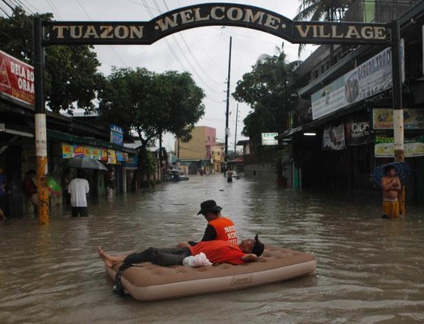 7.ago.2012 - Equipes de resgate descansam em colchão inflável em cidade da região metropolitana de Manila, nas Filipinas, nesta terça-feira (7). Desde o início das fortes chuvas no país, 53 pessoas morreram