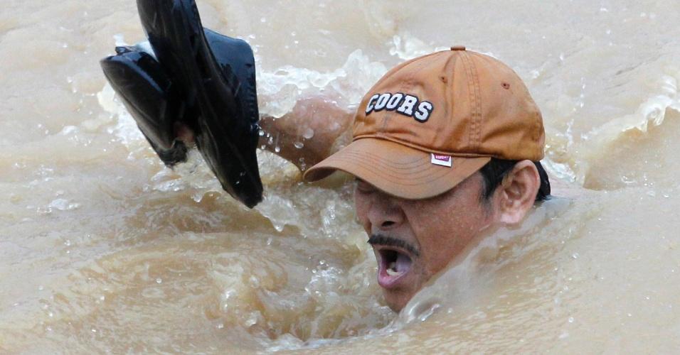 7.ago.2012 -  Homem tenta fugir da correnteza de uma área inundada na região metropolitana de Manila, nas Filipinas, nesta terça-feira (7). Pelo menos 28 mil pessoas tiveram de ser evacuadas a centros de assistência em toda a região de Manila devido às inundações no país