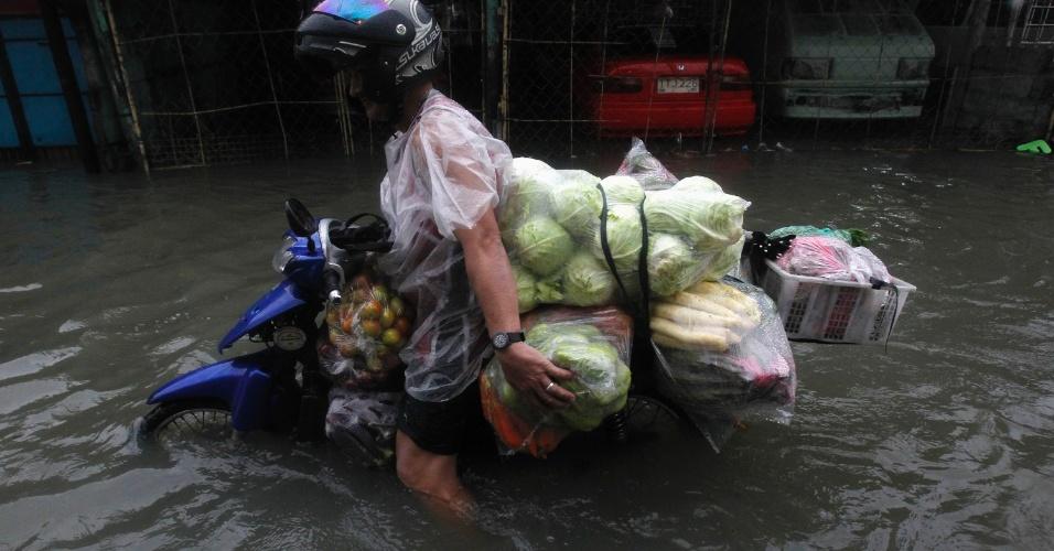 7.ago.2012 - Homem tenta passar por rua alagada de Las Pinas, na região metropolitana de Manila, nas Filipinas, com moto e carregando legumes e vegetais. As inundações voltaram a trazer caos para algumas regiões do país nesta terça-feira (7). Desde o início das fortes chuvas no país, 53 pessoas já morreram
