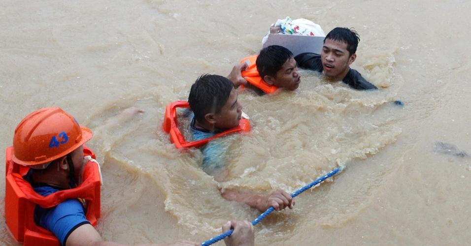 7.ago.2012 - Moradores são resgatados em Marikina, na região metropolitana de Manila, nas Filipinas, nesta terça-feira (7). Pelo menos 28 mil pessoas tiveram de ser evacuadas a centros de assistência em toda a região de Manila devido às inundações no país