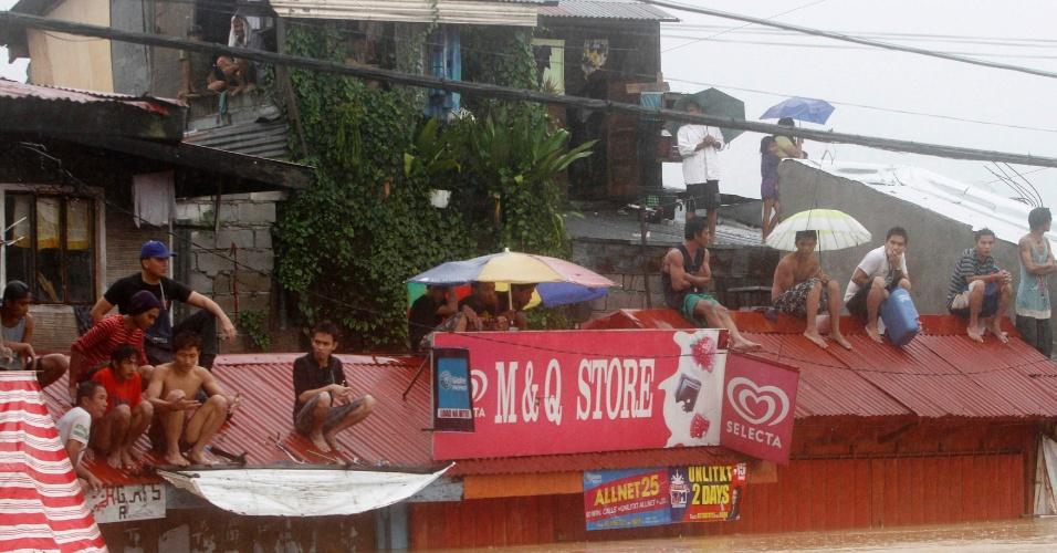 7.ago.2012 - Moradores tentam se proteger das inundações subindo em telhados, em Marikin, região metropolitana de Manila, nas Filipinas. As inundações voltaram a trazer caos para algumas regiões do país nesta terça-feira (7). Desde o início das fortes chuvas no país, 53 pessoas já morreram