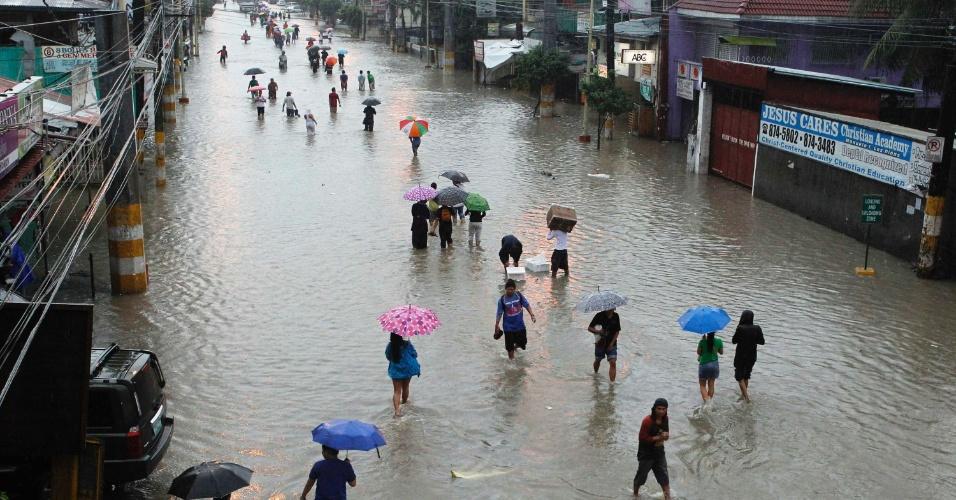7.ago.2012 - Pessoas caminham em rua alagada de Las Pinas, na região metropolitana de Manila, nas Filipinas, nesta terça-feira (7). Desde o início das fortes chuvas no país, 53 pessoas já morreram