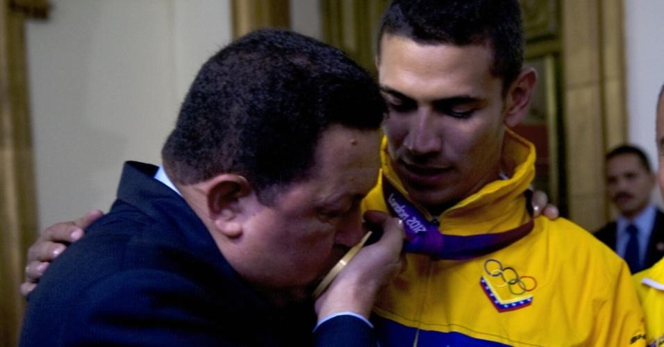 7.ago.2012 - Presidente da Venezuela, Hugo Chávez, beija a medalha de ouro que o esgrimista Ruben Limardo conquistou nos Jogos Olímpicos 2012 durante a chegada do atleta em Caracas