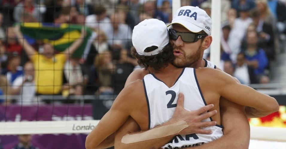 Alison e Emanuel se abraçam para comemorar ponto durante a vitória sobre dupla da Letônia