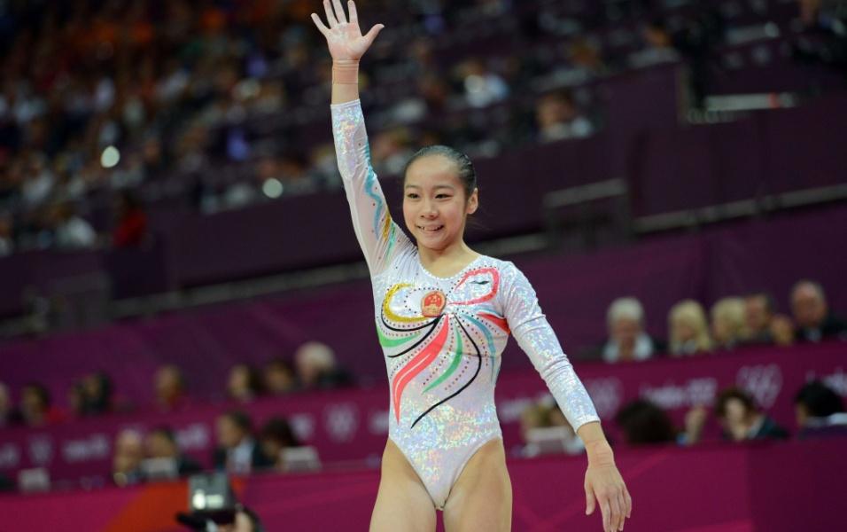 Chinesa Deng Linlin acena para o público após se apresentar na trave; a asiática ficou com a medalha de ouro na prova