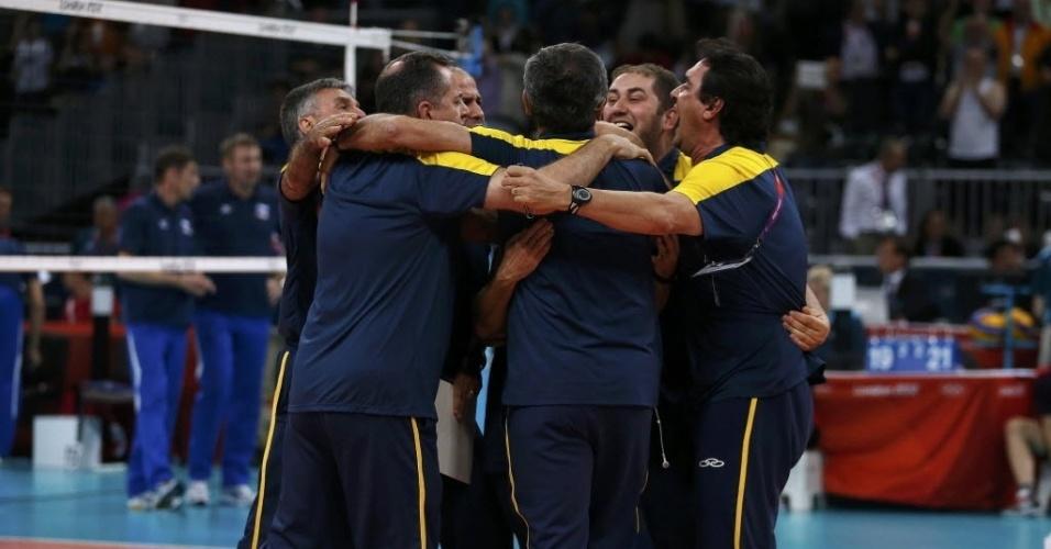 Comissão técnica do Brasil se abraça no centro da quadra depois da vitória contra a Rússia
