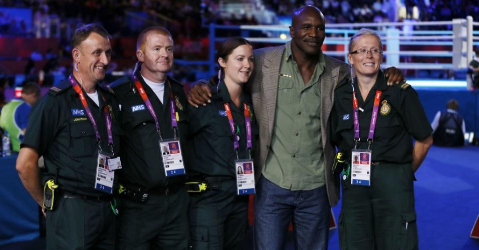 Ex-campeão dos pesos pesados Evander Holyfield faz fotos com voluntários na Excel Arena de Londres, antes de lutas do boxe olímpico