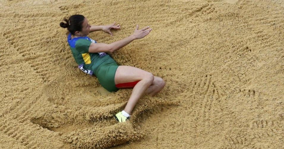 Maurren Maggi cai na caixa de areia após seu primeiro salto, nas eliminatórias do salto em distância