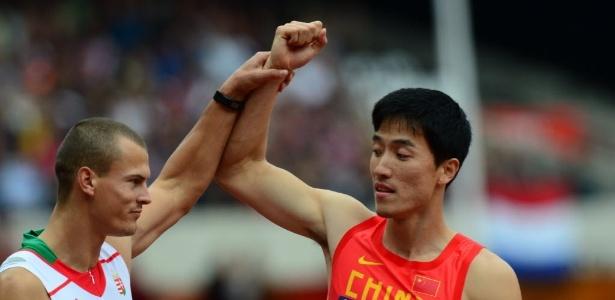 O húngaro Balazs Baji cumprimenta e levanta o braço de Liu Xiang após queda do chinês