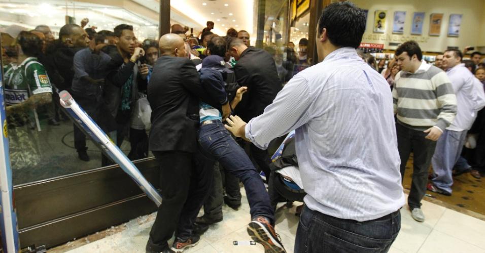 Seguranças reprimem torcedor que tenta qubrar cordão de segurança na porta de livraria em São Paulo